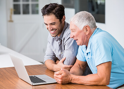 senior father and son working together at computer