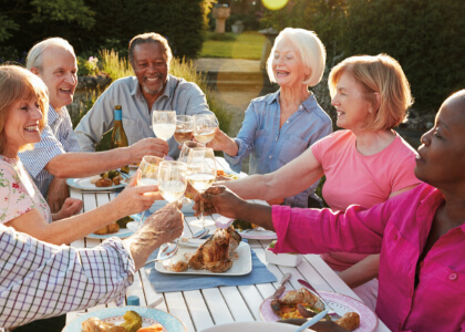 seniors gathered around an outdoor table dining and laughing