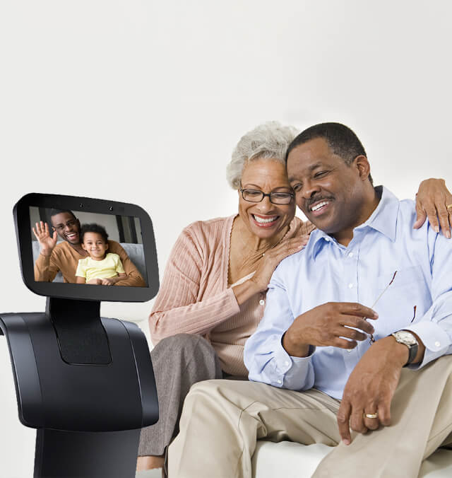 An older Black couple laughing on a video call with family