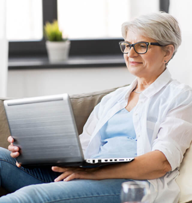 a silver haired woman sits on the couch with her laptop