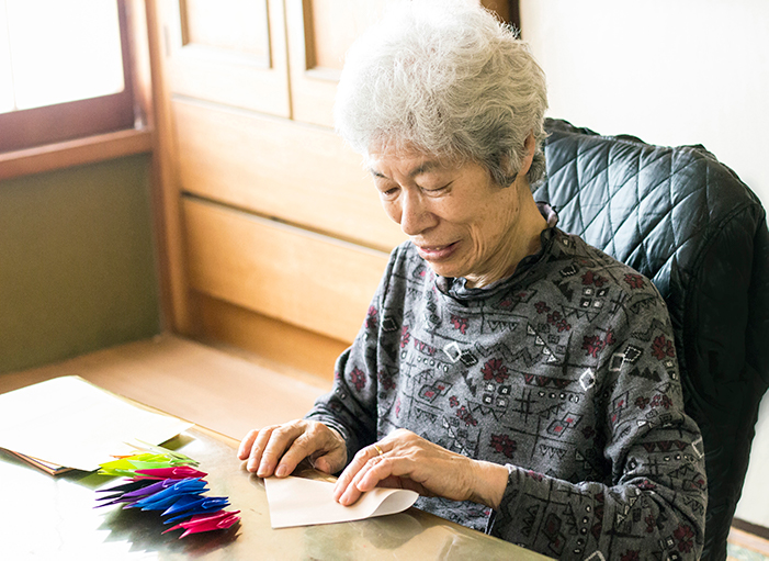 senior woman making an origami crane