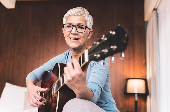 senior woman playing guitar at home