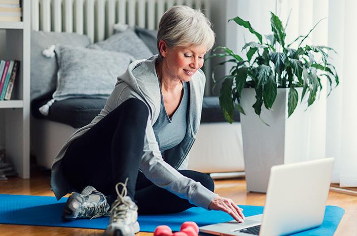 senior woman browsing fitness programs on her laptop
