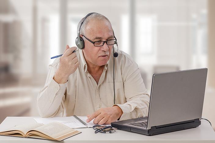 senior man reading on laptop