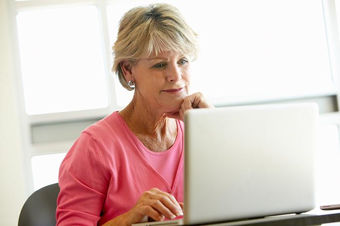 senior woman checking news on a laptop